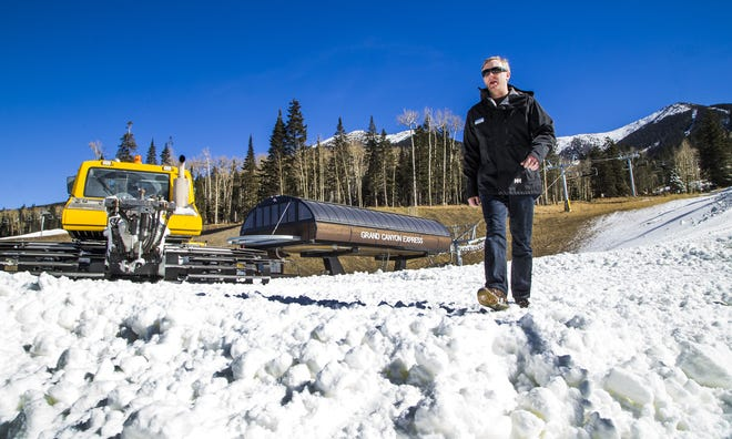 Ryan Hartl, resort services director for Arizona Snowbowl, walks through machine-made snow near the Grand Canyon Express chairlift, Thursday, November 15, 2018.
