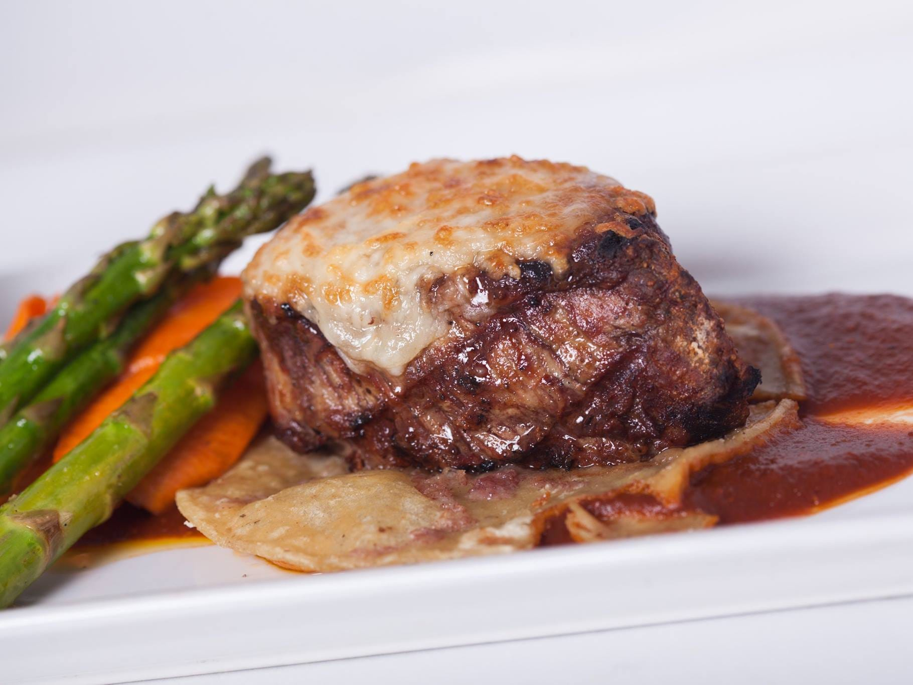 Grilled filet migńon covered with melted manchego cheese, served on a tortilla with potatoes and fresh vegetables.