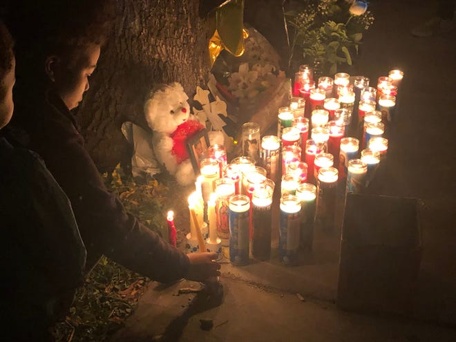 Mourners placed candles, flowers and other mementos at the base of a tree near the site of the crash that killed Keshawn Hubanks.