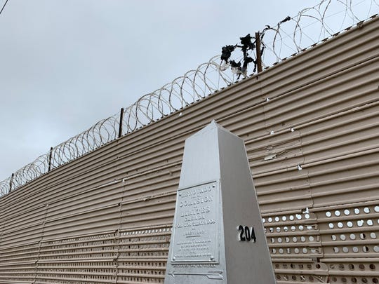 Remnants of plastic sit atop barbed wire installed over landing mat border fencing near the San Luis port of entry.