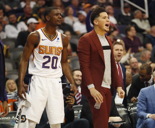 Phoenix Suns forward Josh Jackson (20) and injured guard Devin Booker (1) cheer during the first half against the LA Clippers in Phoenix, Ariz. December 10.