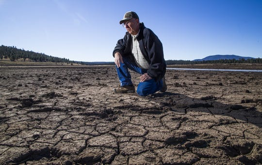 Tom Mackin, Region II director for the Arizona Wildlife Federation, kneels down on the dry, crusted lakebed of Upper Lake Mary in Flagstaff, Thursday, November 15, 2018. Mackin said people were boating in this spot last year.