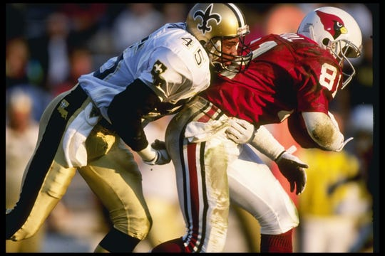 Saints Defensive back Stan Petry tackles Cardinals receiver Randal Hill during a game in 1991 at Sun Devil Stadium.