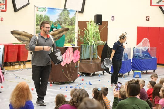 David Stover, left, kindergarten teacher at Bataan Primary, plays the part of a moth during COSI on Wheels' visit to Port Clinton on Tuesday.