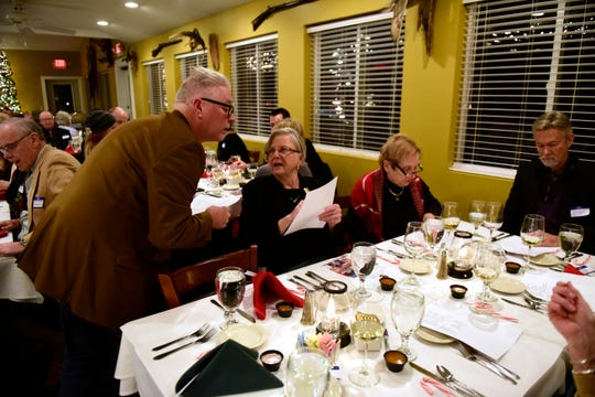 Press Secretary Keith Fleming, left, talks with Marty Willis about officers at the Greater Port Clinton Area Arts Council's annual Christmas dinner at 1812 Food & Spirits in Port Clinton on Monday evening.