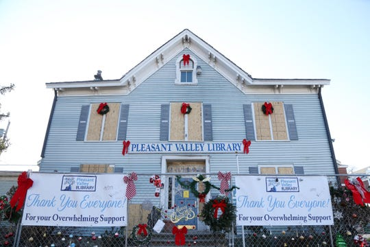 The temporary fence surrounding the boards covered windows and damaged siding of the Pleasant Valley Free Library is decorated with support from the community on December 11, 2018.