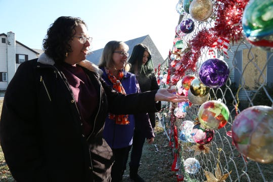 Pleasant Valley Free Library staff members, from left, library director Daniela Pulice, head of borrower services Valerie Britton and circulation assistant Bethany Lowe admire the ornaments from local students outside the fire damaged library building on December 11, 2018.