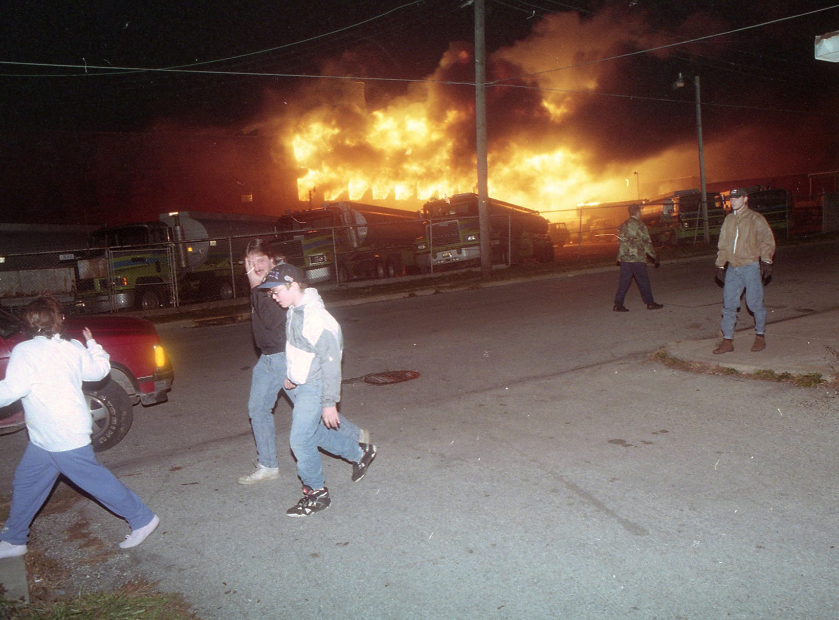People walk past the Shipley tankers in the early stages of the fire. A fire began at the former Thonet Furniture plant at 491 East Princess Street on December 11, 1993. Eventually, the four alarm fire spread through the complex of buildings and several other properties.