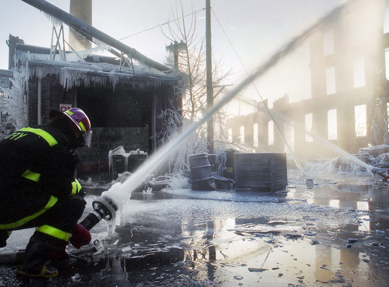 As the sun rises behind the Thonet ruins, a firefighter fights with ice to keep water on the smoldering building. A fire began at the former Thonet Furniture plant at 491 East Princess Street on December 11, 1993. Eventually, the four alarm fire spread through the complex of buildings and several other properties.