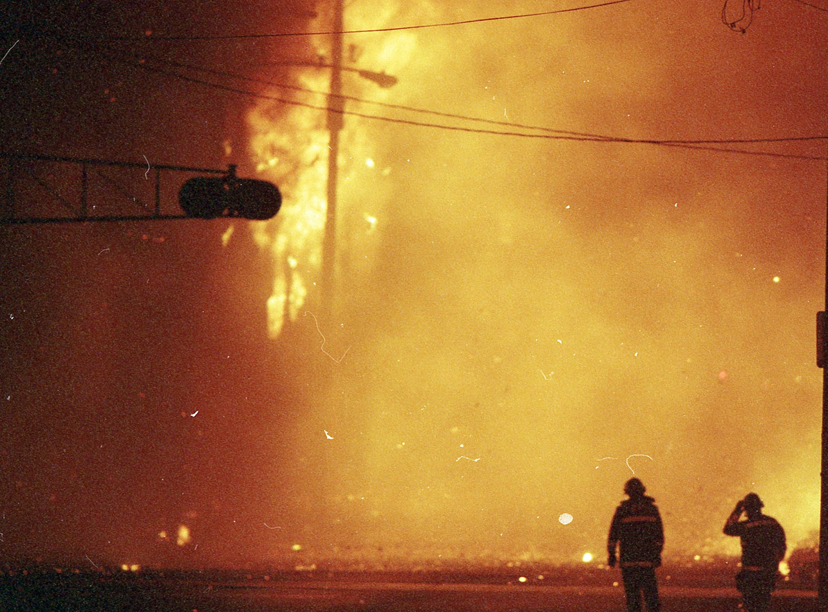 Firefighters are dwarfed by the raging fire. A fire began at the former Thonet Furniture plant at 491 East Princess Street on December 11, 1993. Eventually, the four alarm fire spread through the complex of buildings and several other properties.