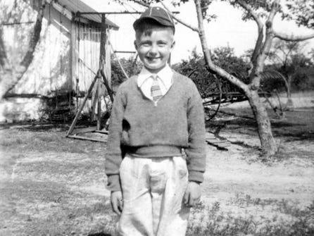 "Richard ""Dick"" Naylor, who was about 10 at the time, poses on his family farm in Anne Arundel County, Md. Dick says he can remember going to the smokehouse (left in photo) on Saturday nights to get salted mackerel out of a wooden tub for his mother to make along with cornbread for Sunday breakfast. After breakfast, his family went to church. Dick says he couldn't wait until church was over and he could get a drink because the mackerel made him so thirsty."