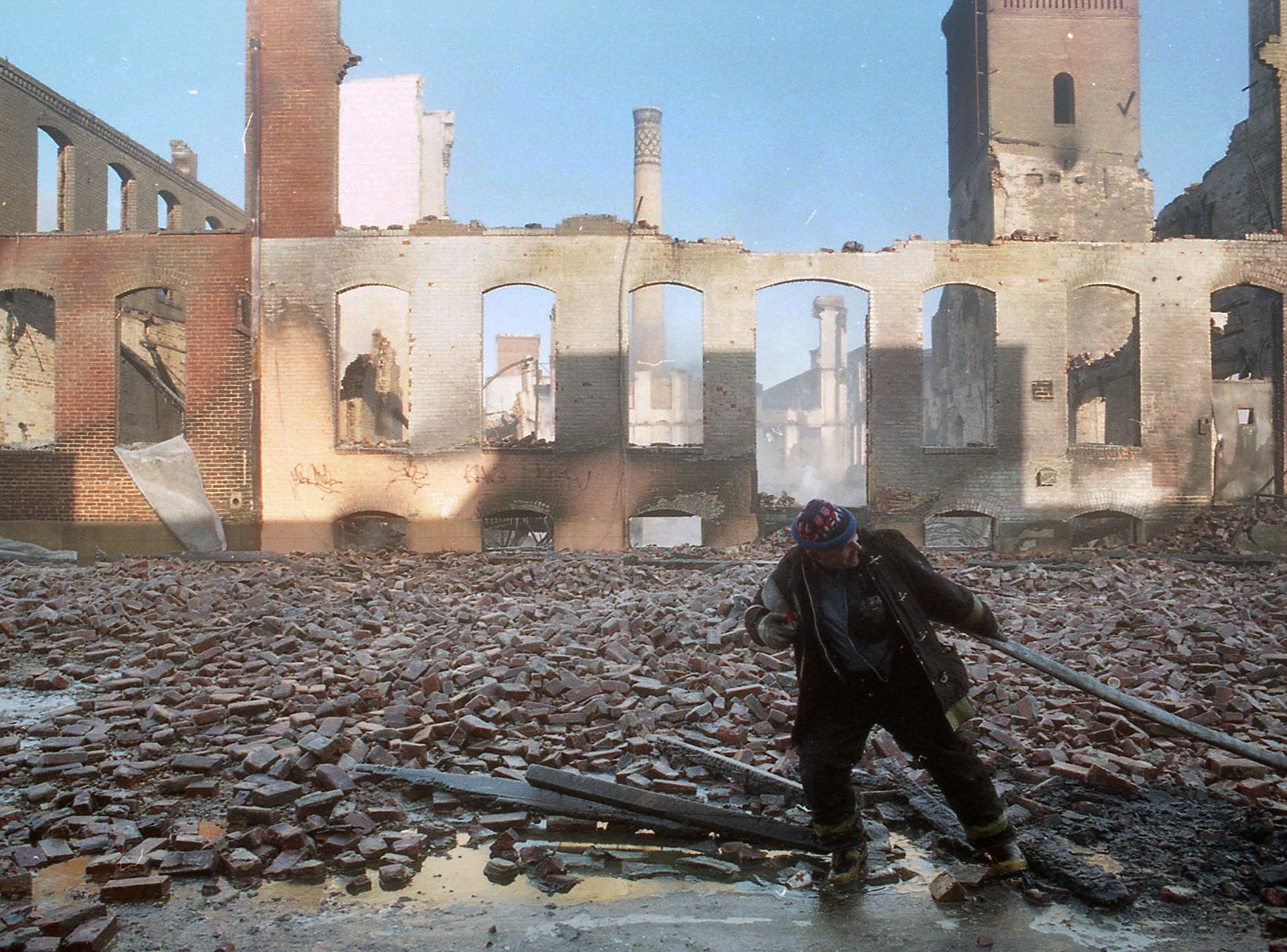 A firefighter pulls a hose in front of the ruins the morning after the fire. A fire began at the former Thonet Furniture plant at 491 East Princess Street in York on December 11, 1993. Eventually, the four alarm fire spread through the complex of buildings and several other properties.