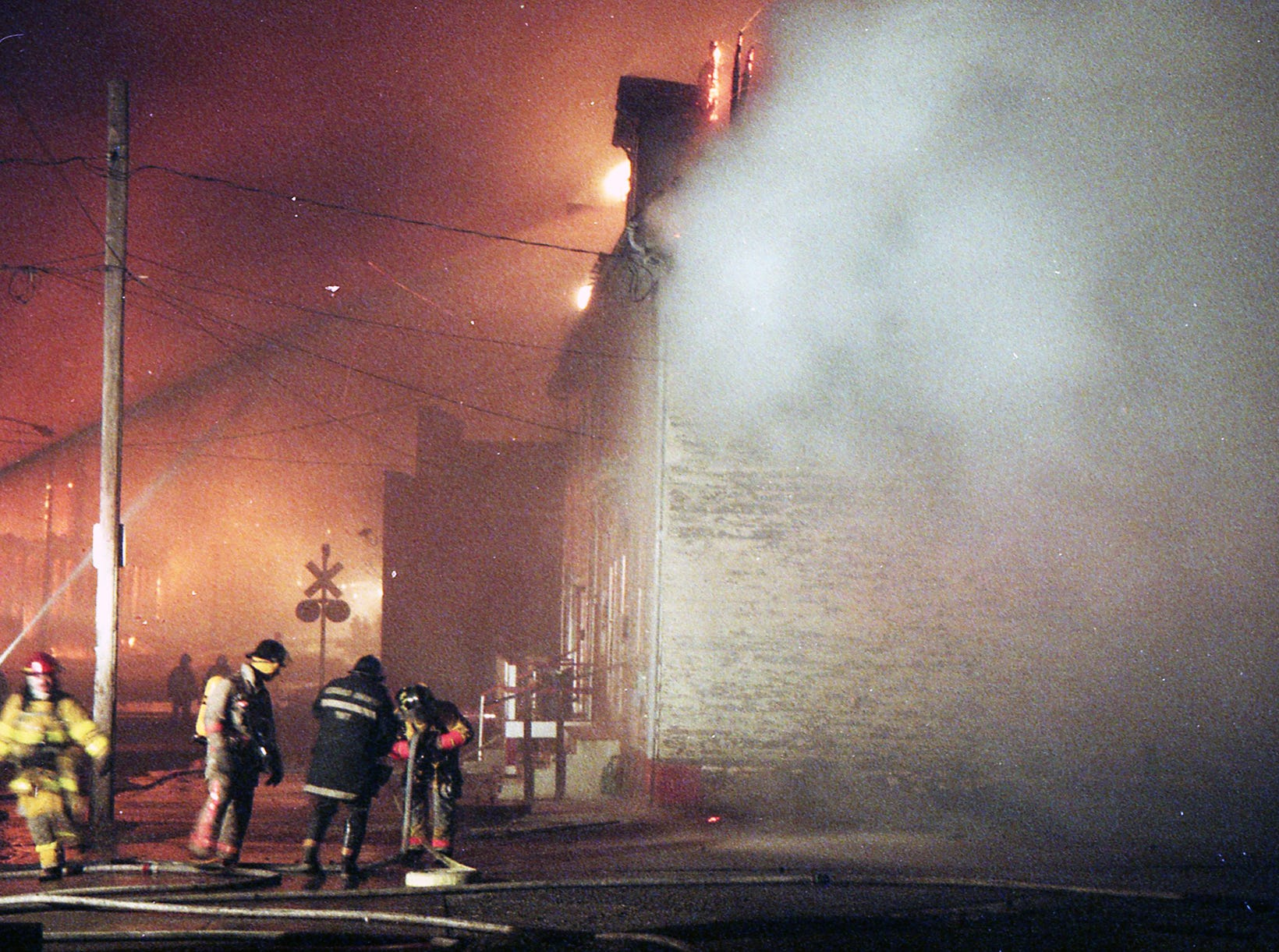 Firefighters attack row houses across the street from the fire that caught fire during the wave of sparks and heat. A fire began at the former Thonet Furniture plant at 491 East Princess Street in York on December 11, 1993. Eventually, the four alarm fire spread through the complex of buildings and several other properties.