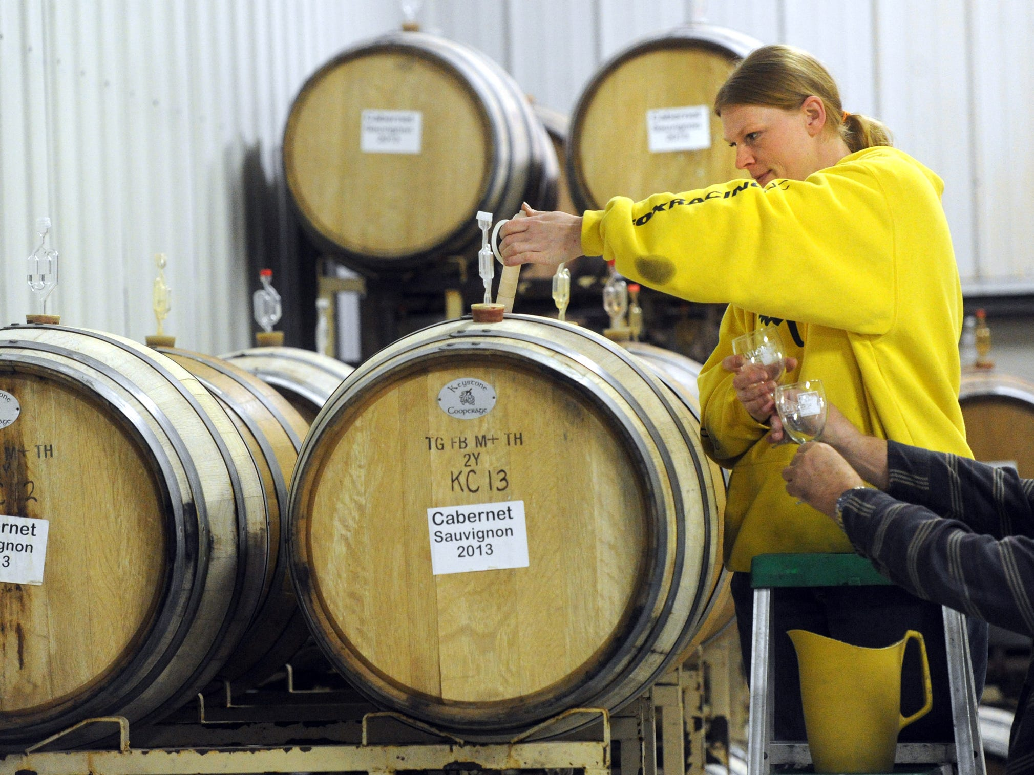 Angel Kellison, the lab technician with Naylor Wine Cellars, samples a barrel of wine with a wine thief in the Stewartstown business on Thursday, Feb. 20, 2014.