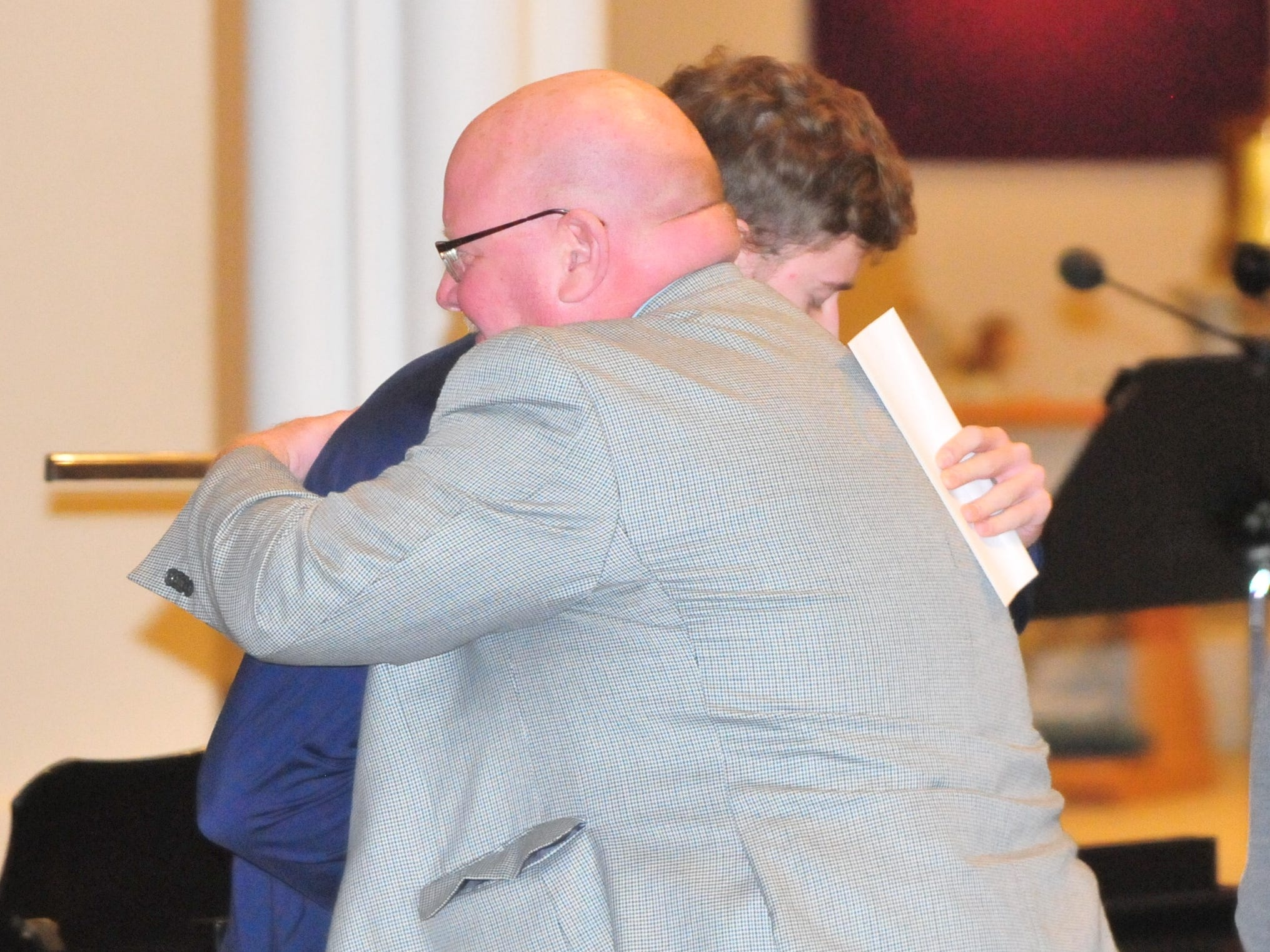 Seton Catholic senior Joseph Lahmann hugs his father Patrick after finding out he won the Lilly Endowment Community Scholarship after morning mass at St. Andrew's Catholic Church in Richmond Tuesday, Dec. 11, 2018.
