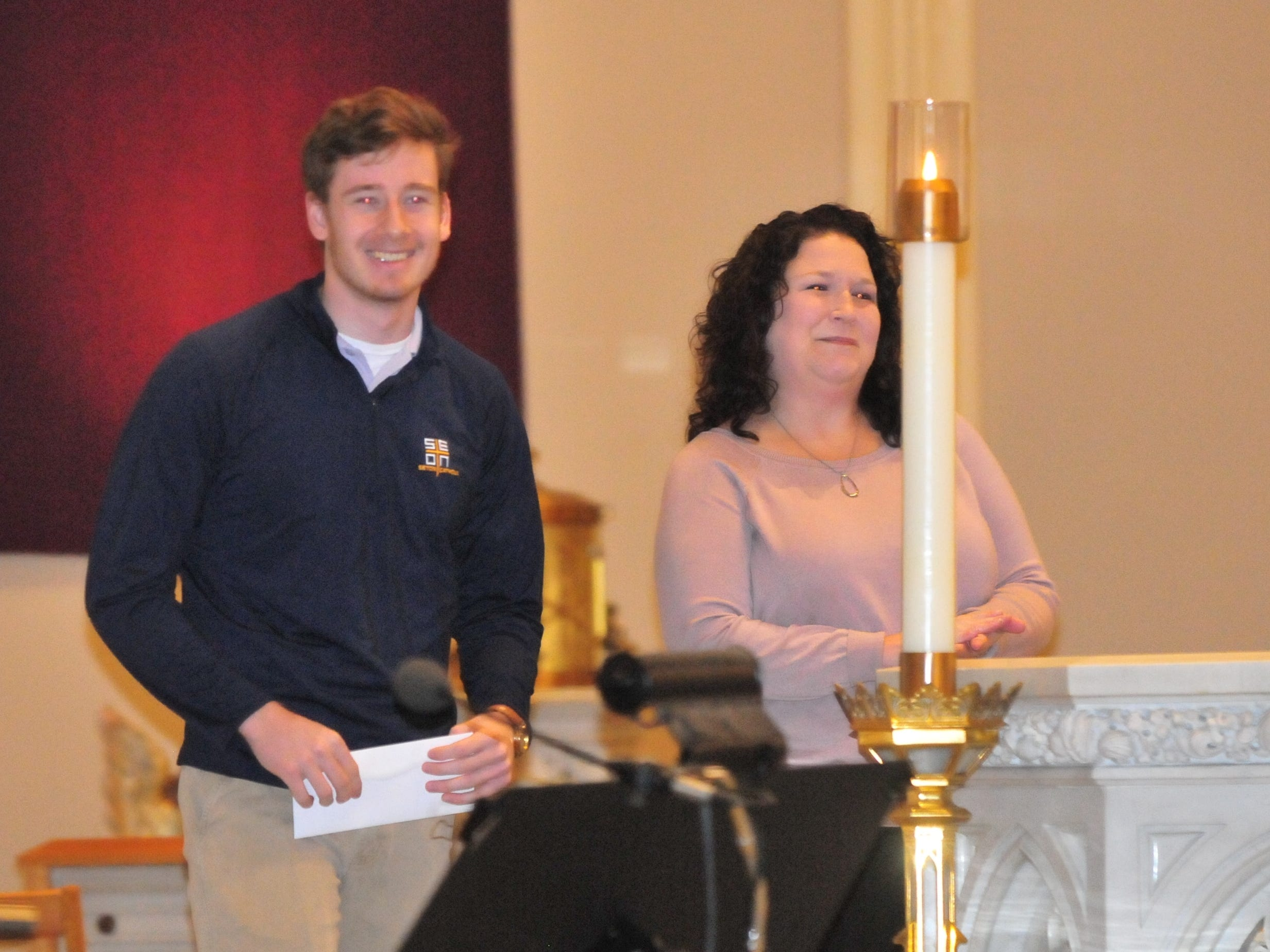 Seton Catholic senior Joseph Lahmann, left, with Wayne County Foundation Program Officer Lisa Bates after finding out he won the Lilly Endowment Community Scholarship after morning mass at St. Andrew's Catholic Church in Richmond Tuesday, Dec. 11, 2018.