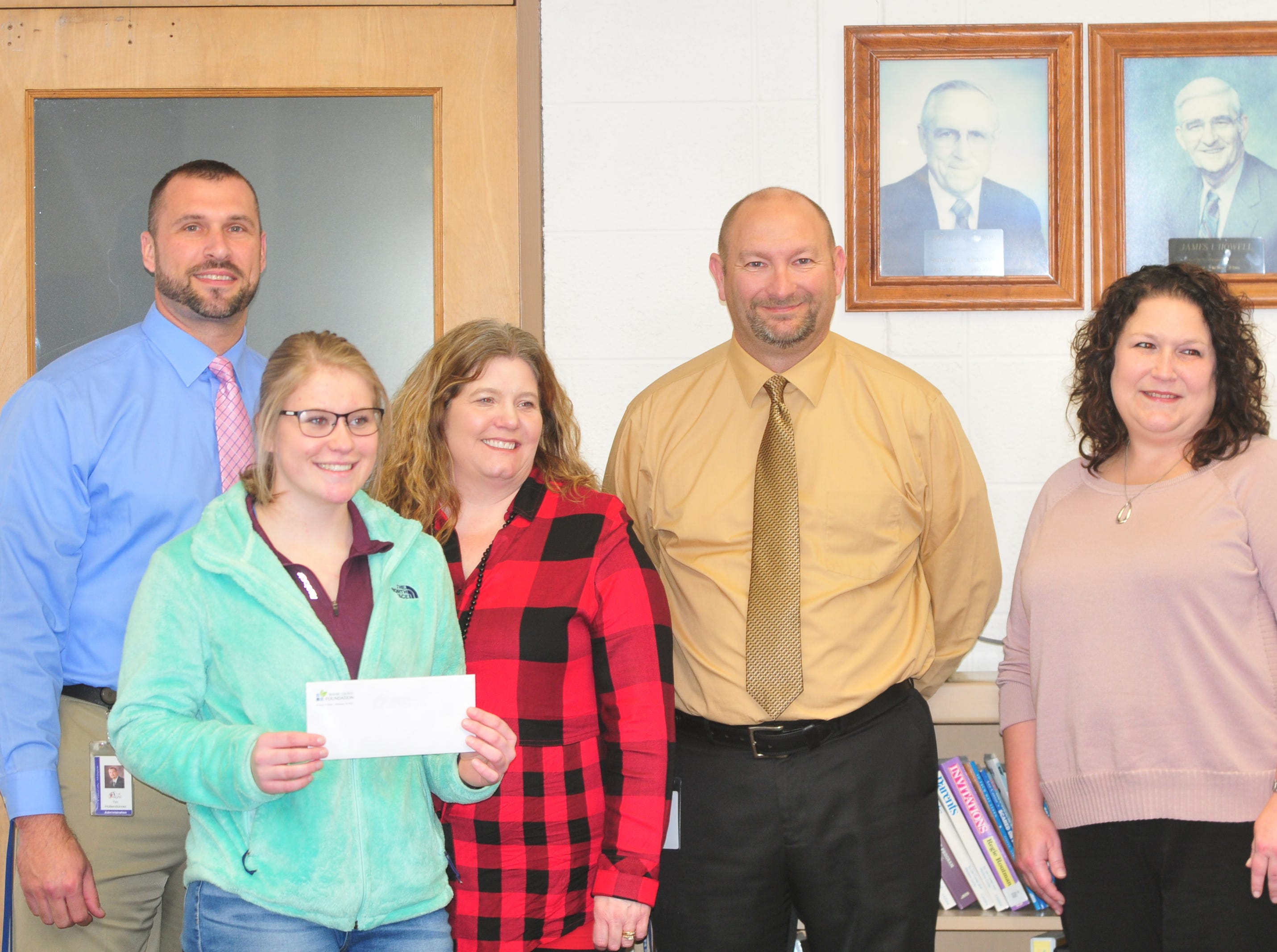 Centerville High School senior Molly Coomes, second from left, with assistant principal Tim Hollendonner, mother Renee Westover, principal Mike McCoy and Wayne County Foundation Program Officer Lisa Bates after learning that Coomes is a recipient of the Wayne County Foundation's Lily Endowment Community Scholarship at Centerville High School Tuesday, Dec. 11, 2018.