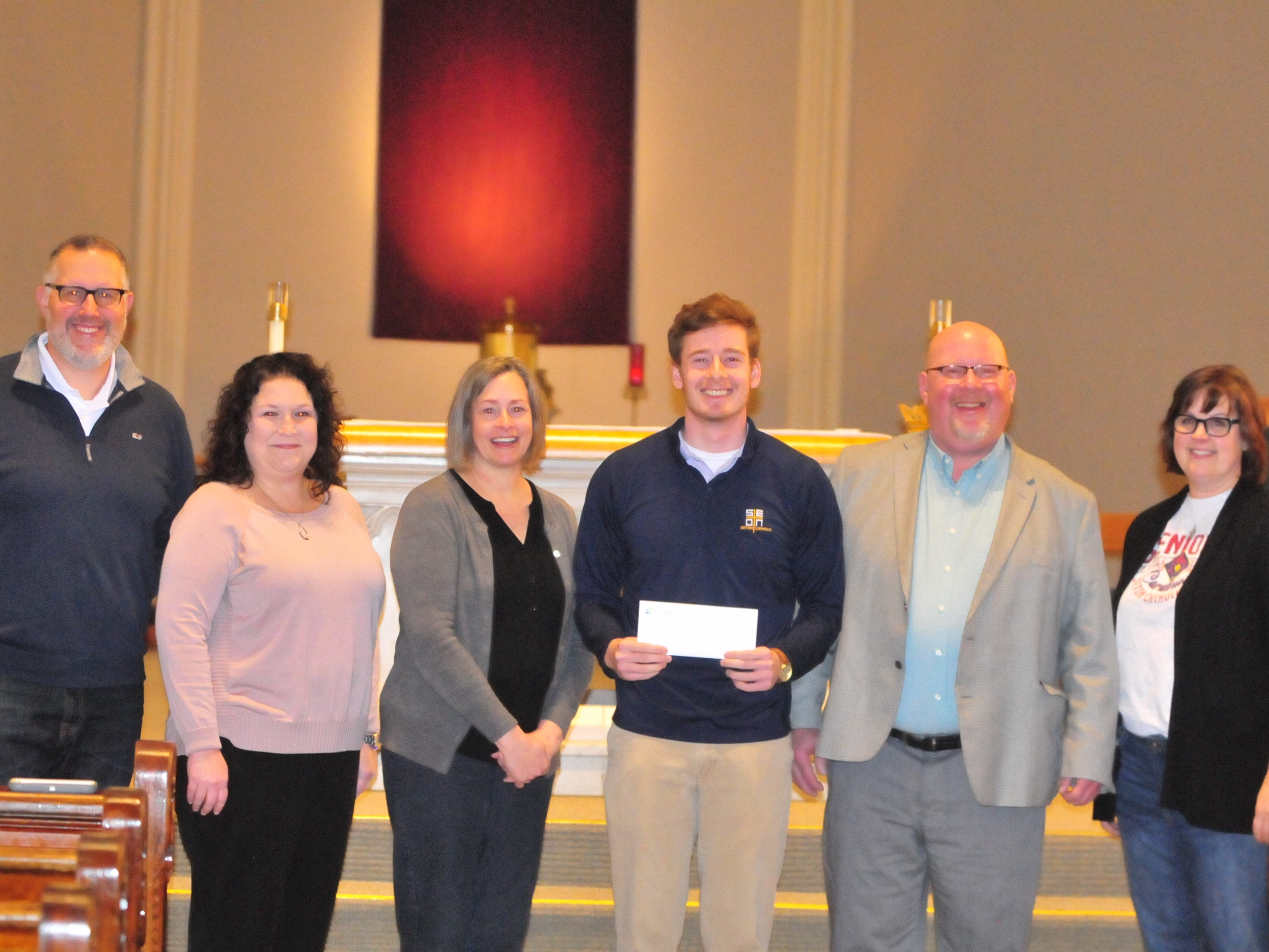Seton Catholic senior Joseph Lahmann, third from right, with principal John Markward (from left), Wayne County Foundation Program Officer Lisa Bates, mother Margaret Rees Lahman, father Patrick Lahmann, and guidance counselor Shantel Cartwright after finding out Joseph won the Lilly Endowment Community Scholarship after morning mass at St. Andrew's Catholic Church in Richmond Tuesday, Dec. 11, 2018.
