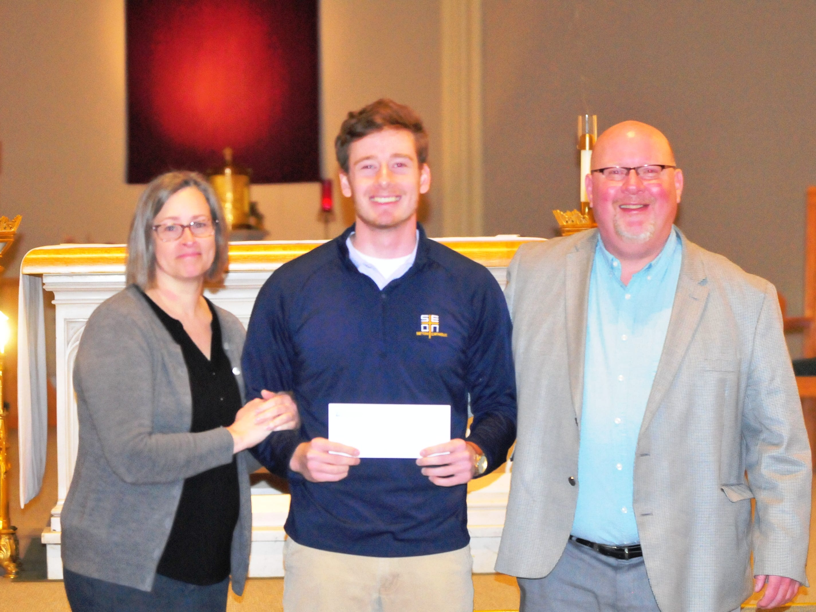 Seton Catholic senior Joseph Lahmann, center, with mother Margaret Rees Lahmann, left, and father Patrick Lahmann, after finding out Joseph won the Lilly Endowment Community Scholarship after morning mass at St. Andrew's Catholic Church in Richmond Tuesday, Dec. 11, 2018.