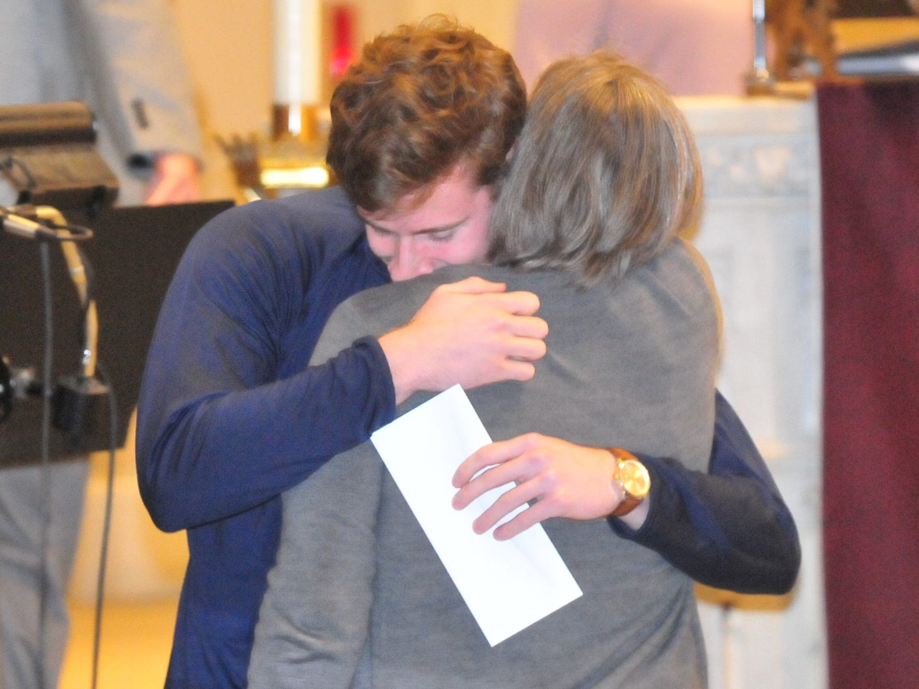 Seton Catholic senior Joseph Lahmann, hugs his mother Margaret Rees Lahmann after finding out he won the Lilly Endowment Community Scholarship after morning mass at St. Andrew's Catholic Church in Richmond Tuesday, Dec. 11, 2018.