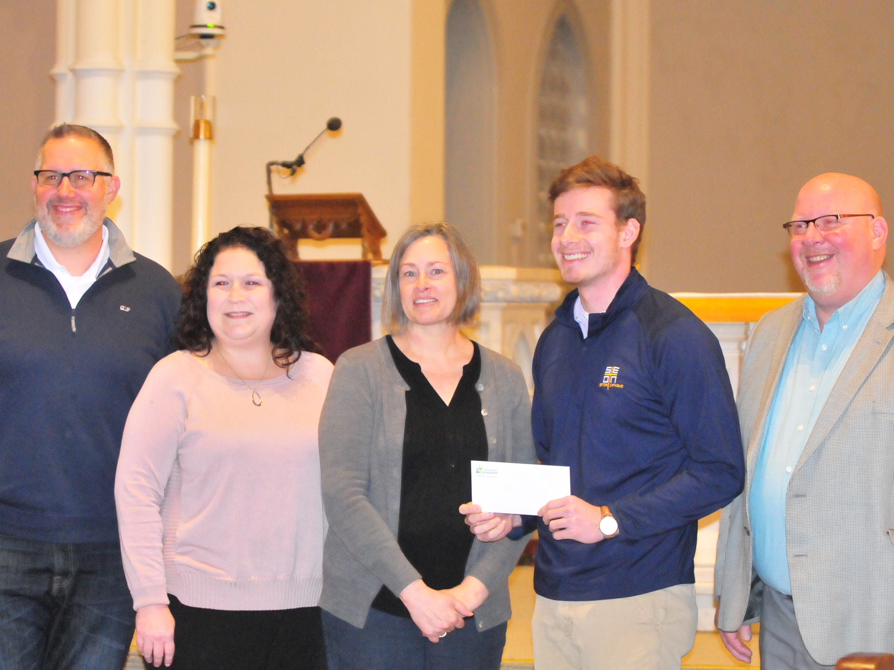 Seton Catholic senior Joseph Lahmann, fourth from left, with principal John Markward, Wayne County Foundation Program Officer Lisa Bates, mother Margaret Rees Lahman, and father Patrick Lahmann, after finding out Joseph won the Lilly Endowment Community Scholarship after morning mass at St. Andrew's Catholic Church in Richmond Tuesday, Dec. 11, 2018.