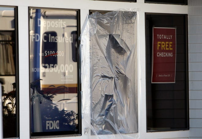 A taped over window is seen at West Coast Bank Dec. 15, 2008, in Woodburn, Ore. Many questions remain in a bombing that killed two officers and critically injured a police chief at an Oregon bank.