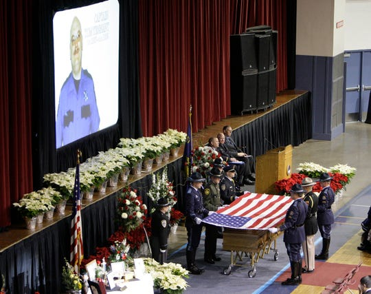 Police officers pay respect during a memorial service for 51-year-old Woodburn Police Capt. Tom Tennant Dec. 19, 2008, at the Salem Armory, in Salem, Ore. Tennant was a 28-year veteran of the Woodburn police force and was killed in the bank bombing.