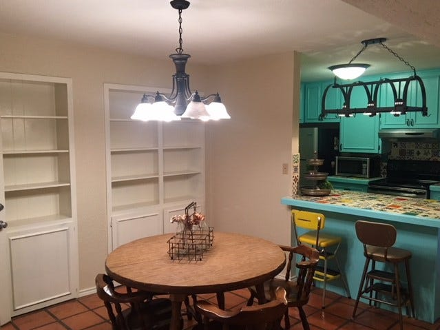 This view at 2566 Sunset Drive shows the dining room and a peek at the blue kitchen with hand-painted tiles.