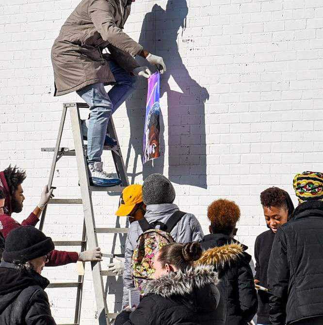 Carmall Washington helps to assemble a mural of Black Panther's T'Challa created by the Envision art club at University of Maryland Eastern Shore in Princess Anne on Tuesday, Dec 11, 2018.