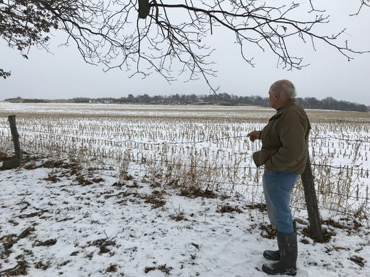 Frank Boll stands at the edge of his land, looking at the neighboring property where mining operations are expected to resume in 2019.