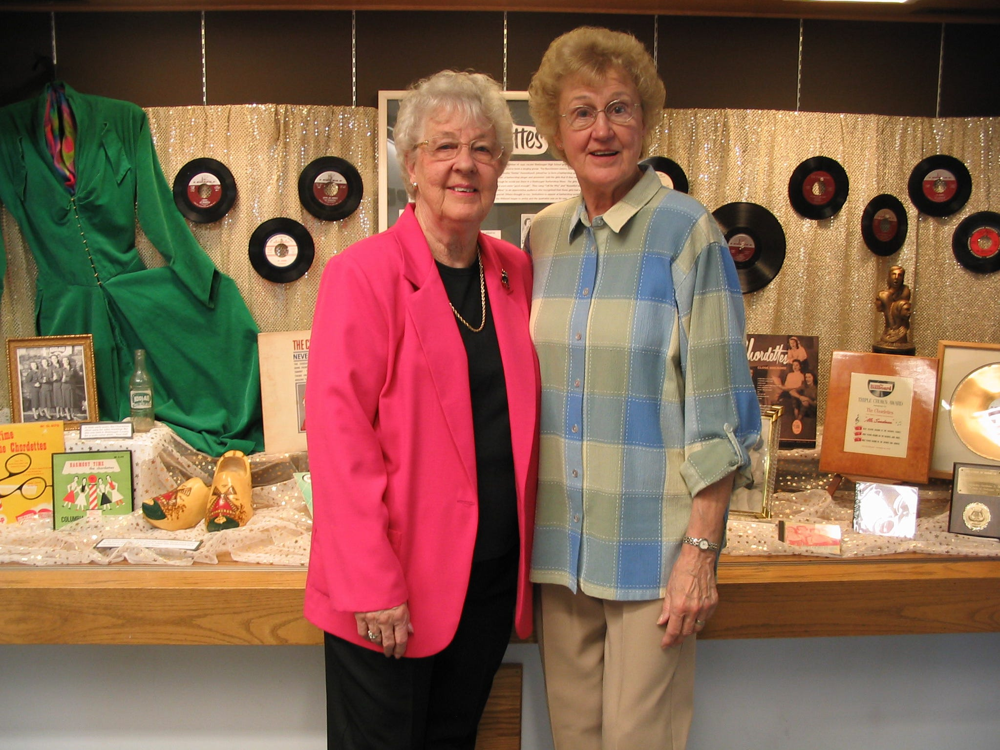 Carol Buschmann, left, and Dorothy Schwartz of the Chordettes pose, Monday, August 16, 2004, with their Mead library exhibit.
