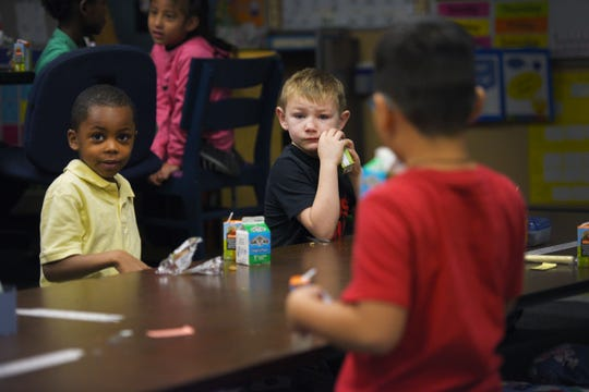 First grade students Henry Barlue, left, and Morgan Maunu, right, eat breakfast before class starts Monday, Dec. 10, at Terry Redlin Elementary School in Sioux Falls.