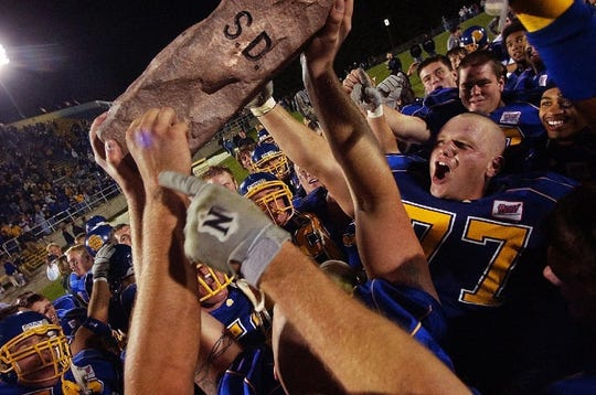 Taylor Murray (77) and his Jackrabbbit teammates raise the Dakota Marker Trophy following a come-from-behind win over North Dakota State University in the 38th Annual Beef Bowl in Brookings Saturday, Oct. 9, 2004.