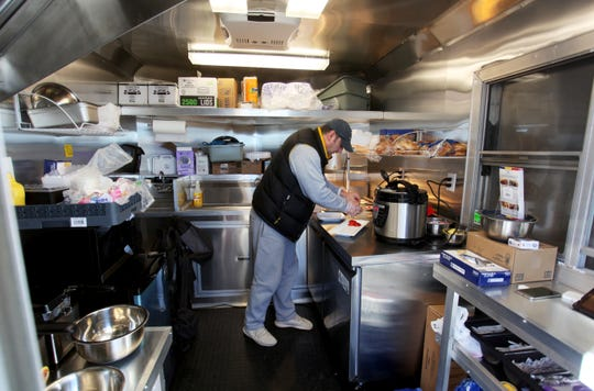 Romulus Manole sets a plate at his food truck, Dacia. He and his wife, Hannelore, opened the truck in August.