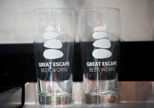 A pair of pint glasses sit near the bar inside of Great Escape Beer Works which is located at 4022 S. Lone Pine Ave. in Quarry Town.