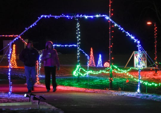 People walk along the lighted trail around Lake Francis Park during the Country Lights Festival Friday, Dec. 7, in Sartell.