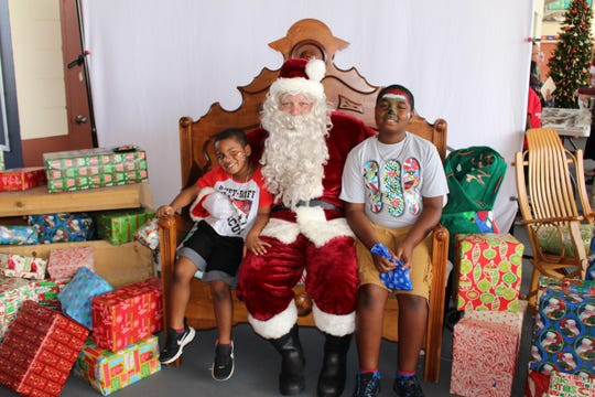 Ethan, 5, and Jacob, 8, tell Santa (Kevin Lake) what they want for Christmas before heading off to enjoy breakfast and other activities.