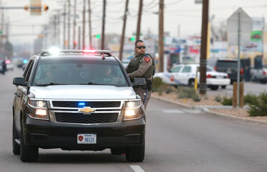Officers search for a man after he shot an officer in the hand Tuesday, Dec. 11, 2018. Officers stopped the man because of suspicious behavior when the altercation began. Students at Cooley Elementary School were helped to buses after school and were bused to Henderson Middle School for parents to pick up.