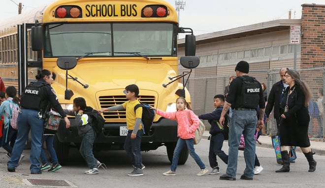 Officers search for a subject after her shot an officer in the hand. Officers stopped the man because of suspicious behavior when the altercation began. Students at Cooley Elementary School were helped to buses after school and were bussed to Henderson Middle School for parent pick up.