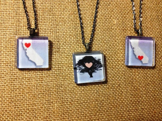 "The ""Love for California"" collection consists of three pendants, from left: one with a heart in Northern California where the Camp Fire destroyed the small town of Paradise, one featuring a city of Thousand Oaks tree with a heart in the center and one depicting the state of California with a heart in the location of the Woolsey and Hill Fires. This collection was created by Nancy Kanter, owner of Sparkling Vine Design in Newbury Park, and 100 percent of profits go to victims of the shooting at Borderline Bar & Grill in Thousand Oaks and fire victims."