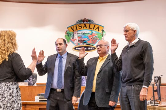 Councilmen Greg Collins, right, Steve Nelsen and Brian Poochigian take the oath of office from Chief Deputy City Clerk Michelle Nicholson during the Visalia City Council meeting on Monday, December 10, 2018.