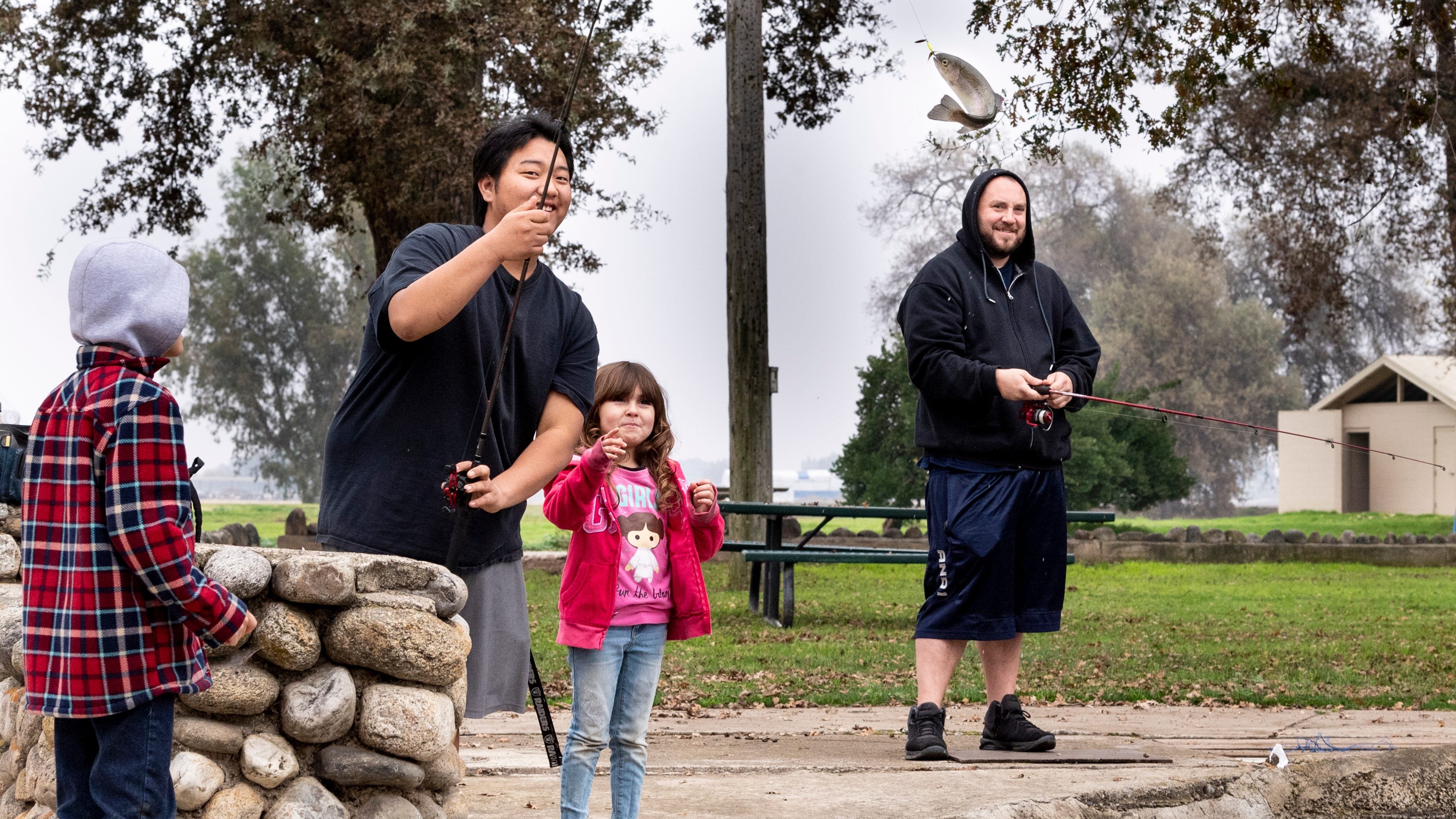Nathen Hughes, right, and his children Shyleigh Hughes, 6, and Harley Hughes, 8, watch Johnny See catch the first  fish after 500 pounds of rainbow trout were released into the pond at Mooney Grove Park on Tuesday, December 11, 2018. They range in size from about 3/4 pound to 1 1/2 pounds. The pond will be restocked every two weeks until March.