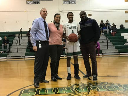 Woodlands girls basketball senior Teisha Hyman poses with her parents and Woodlands athletic director Michael McCoy after breaking the school scoring record on Dec. 10, 2018.