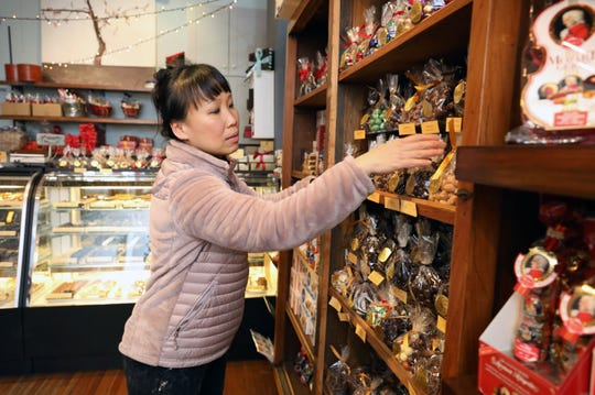 "Julia Dillon, owner of Tree of Chocolate in Nyack, arranges some bagged chocolate pieces on a shelf in her shop, Dec. 11, 2018. ""Usually right after Thanksgiving, people just start coming in and right away get items, but I think with Thanksgiving being a little earlier this year, that it started a little slower.  Chocolates, especially for our store, people still like to get it and to see it, you know, like the items instead of going online."""