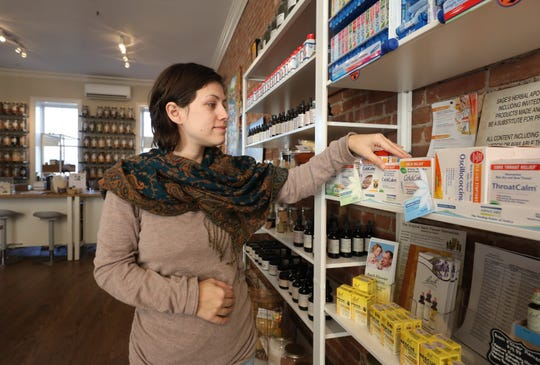 Sarah Bergmann, co-owner of Sage's Herbal Apothecary in Nyack, arranges some  homeopathic items in her shop.