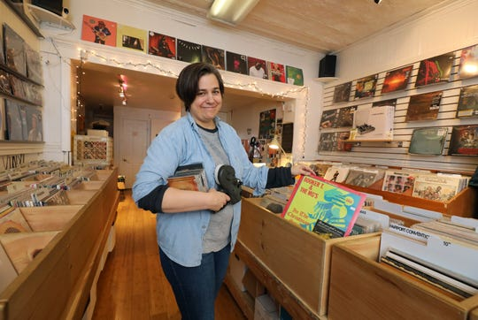 """Jennifer O'Connor, co-owner of Main Street Beat, shows off a vinyl Christmas album by Booker T & the MG's in her shop in Nyack, Dec. 11, 2018. """"The holiday shopping season is going great so far. And we're open every thru Christmas, up until Christmas, and we're expecting it to get busier and busier, each day."""""""
