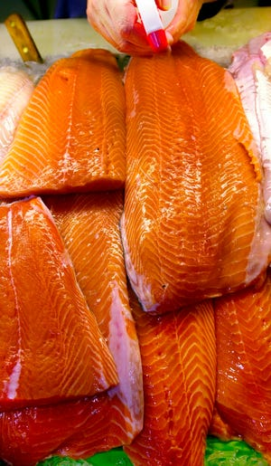 Fillets of farm-raised salmon are sprayed with water at a local fish market in Portland, Maine. The Food and Drug Administration notes that manufacturers have to declare on labeling if color additives were used for salmon.