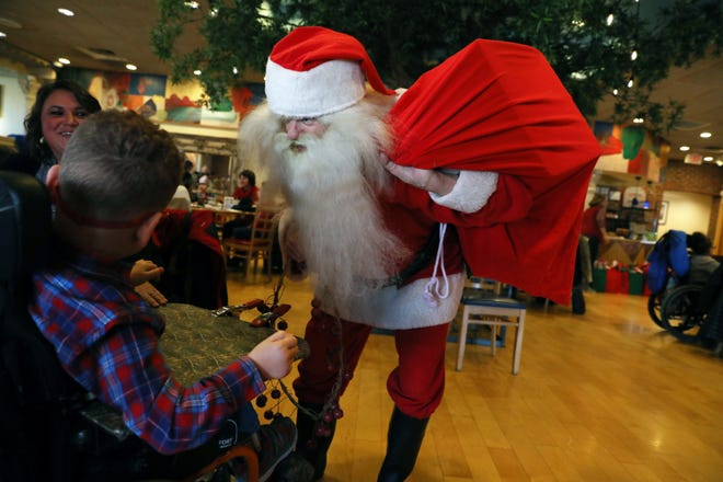 Santa greets a youngster at the Rotary Club's annual Christmas party for children at Adornetto's on Tuesday.