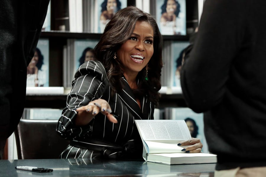 "Former first lady Michelle Obama signs copies of her book ""Becoming"" in New York on Nov. 30, 2018."
