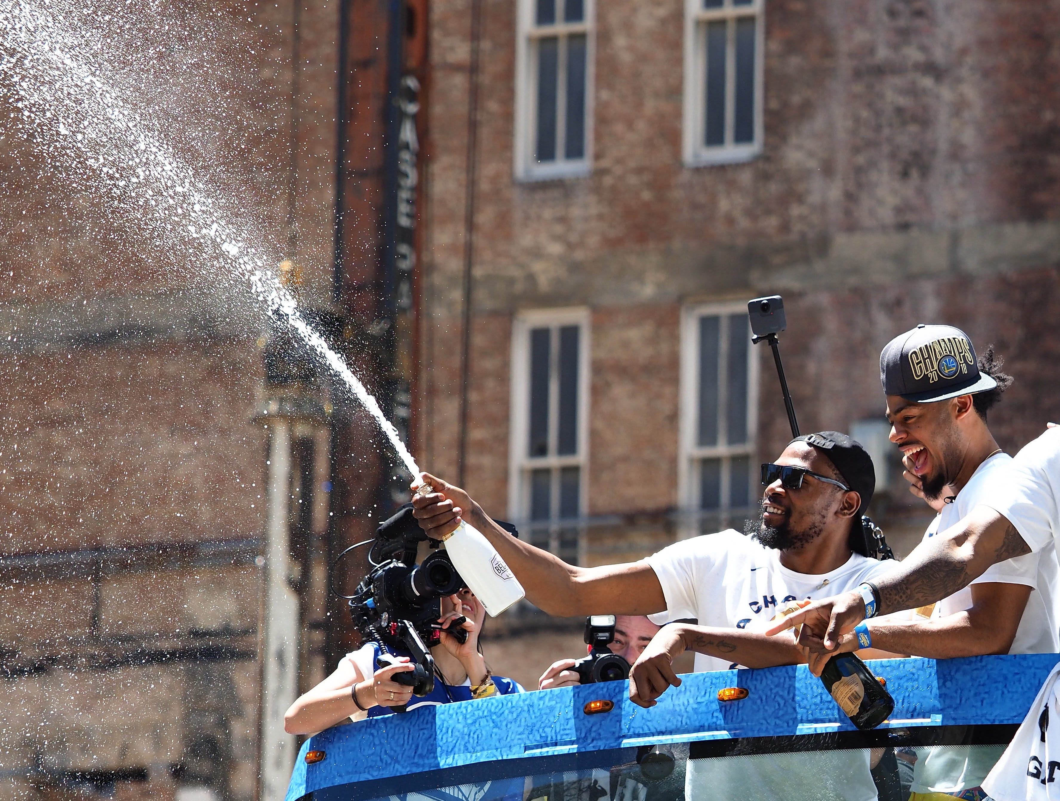 June 12: Golden State Warriors forward Kevin Durant sprays champagne during the championship parade in downtown Oakland.